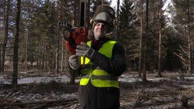 Lumberjack с цепной пилой на плече в лесе с трясти камеры видеоматериал