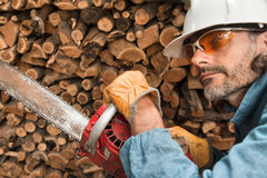 Lumberjack. Close up with chainsaw, forest worker in action Stock Photo