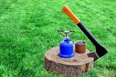 Lumberjack Axe, Gas Burner, Tea Mug on Tree Cross Section Royalty Free Stock Photos