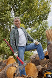 Lumberjack with an axe standing with stack of chopped firewood in background Royalty Free Stock Image