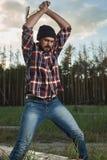 Lumberjack with Beard, Hat and Shirt swings the ax Stock Photo