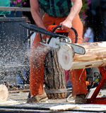 Lumberjack chainsaw. A lumberjack powers through a log with a chainsaw stock images