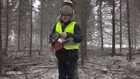 Lumberjack with chainsaw in forest in snow storm stock footage