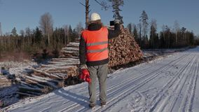 Lumberjack with chainsaw take pictures on smart phone. In winter day stock video