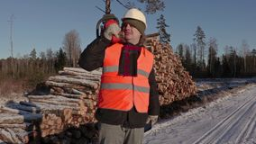 Lumberjack with chainsaw talking on phone near pile of logs in winter. Day stock video