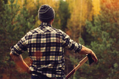 Lumberjack in checkered shirt and ax. At the forest Royalty Free Stock Photography