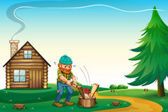 A lumberjack chopping the woods at the hilltop near the wooden h Stock Image