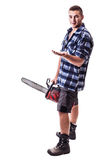 Lumberjack endorsing something. A young lumberjack wearing a checkered shirt holding a chainsaw and showing something isolated over white background royalty free stock images