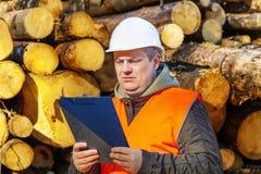 Lumberjack in forest. Near logs with folder Stock Image