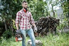 Lumberjack lub woodcutter chodzenie i patrzeć z piłą łańcuchową Fotografia Stock