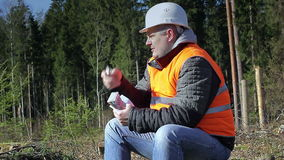 Lumberjack with money and cell phone in forest stock footage