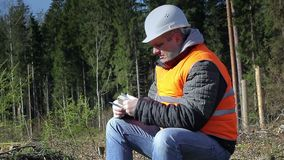 Lumberjack with money talking on the cell phone in forest stock footage
