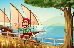 A lumberjack near the fence at the riverbank with a ship Stock Image