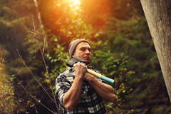 Lumberjack posing with ax. Sunlight efect Royalty Free Stock Photography