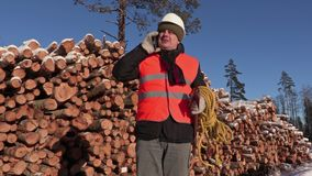 Lumberjack with rope and ax talking on phone near pile of logs in winter. Day stock footage