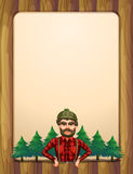 A lumberjack standing in front of the pine trees Royalty Free Stock Image