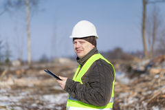 Lumberjack with tablet PC. In cleared forest in winter Royalty Free Stock Photos