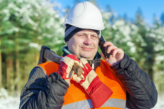Lumberjack talking on cell phone in forest Royalty Free Stock Photo