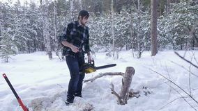 Lumberjack tries to start manual chainsaw. Lumberjack tries to start a chainsaw hand, he stands in a winter snow-covered forest stock video