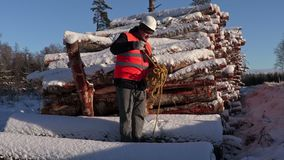 Lumberjack try collect rope near pile of snow covered logs in winter stock video footage