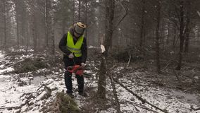 Lumberjack trying to start chainsaw in forest stock video