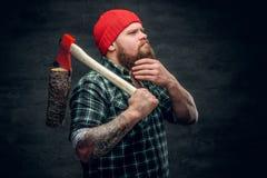 Lumberjack ubierał w koszula zielonych chwytach czerwoną cioskę Fotografia Stock