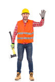 Lumberjack waving hand. Lumberjack in yellow helmet and orange waistcoat standing with an axe and showing open hand, Front view. Full length studio shot isolated Stock Photo