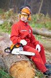 Lumberjack Worker With Chainsaw In The Forest. Lumberjack Worker in protective safety work wear With Chainsaw at Forest stock photography