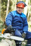 Lumberjack worker with chainsaw in the forest Royalty Free Stock Photography