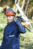 Lumberjack worker with chainsaw in the forest Royalty Free Stock Images