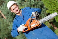 Lumberjack Worker with Chainsaw in Work Wear on Forest background Stock Image