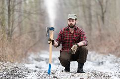 Lumberjack worker standing in the forest with axe Royalty Free Stock Images