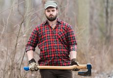 Lumberjack worker standing in the forest with axe Royalty Free Stock Photo