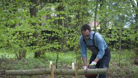 Lumberjack in workwear saws firewood on sawhorses with electric saw. Forest.