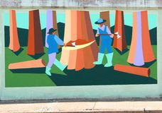 Lumberjacks Mural On James Road in Memphis, Tennessee. Beautiful local artist mural rendering of Wood Cutters chopping down a large tree on a bridge underpass Royalty Free Stock Photography