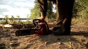 Lumberman que liga a serra de cadeia para a lenha vendo vídeos de arquivo