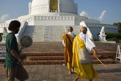 Lumbini, Nepal 17 de setembro de 2013: Os peregrinos rezam no pagode da paz de Lumbini imagens de stock royalty free