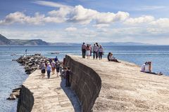 Lume Regis Dorset UK The Cobb. 1 July 2017: Lyme Regis, Dorset, England, UK - Visitors enjoying the good weather on The Cobb stock image