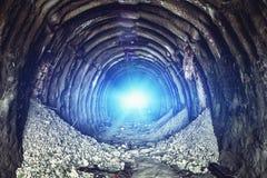 Lumière bleue mystérieuse à la fin de vieux tunnel industriel rond ou de couloir de mine souterraine photo stock