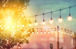 Lumière brouillée sur le coucher du soleil avec le décor de lumières de ficelle dans le restaurant de plage images stock