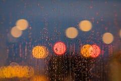 Lumière d'égaliser des baisses de ville et de pluie sur la fenêtre Fond brouillé par abstrait photos stock