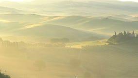 Lumière d'or naturelle avec le brouillard le soir du paysage accidenté au champ toscan dans la saison d'été clips vidéos