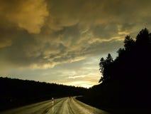 Lumière d'or, routes humides, nuages de tempête, motos Photos libres de droits