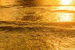 Lumière d'or se reflétant outre d'une vague d'eau à la mer et du sable sur le coucher du soleil Photos stock