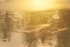 Lumière d'or se reflétant outre d'une vague d'eau à la mer et du sable sur le coucher du soleil image libre de droits