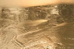 Lumière d'or se reflétant outre d'une vague d'eau à la mer et du sable sur le coucher du soleil image stock