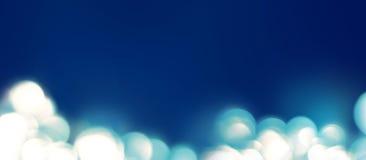 Lumière dans un defocused Les taches Boke sur le bleu colore le fond abstrait Image libre de droits