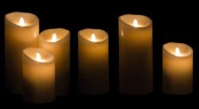 Lumière de bougie, trois lumières de bougies de cire sur le fond noir Image stock