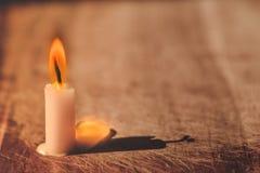 Lumière de flamme de bougie sur le vieux bois avec l'éclairage sur la fenêtre Images libres de droits
