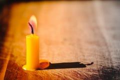 Lumière de flamme de bougie sur le vieux bois avec l'éclairage sur la fenêtre Image libre de droits
